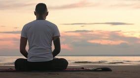 Uomo flessibile nella posa del loto che medita su spiaggia stock footage