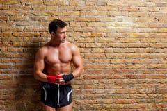Uomo a forma di del pugile del muscolo con la fasciatura del pugno Fotografie Stock
