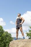 Uomo forte atletico che sta su un distogliere lo sguardo della roccia immagini stock libere da diritti