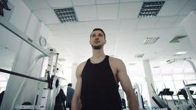Uomo forte che cammina attraverso la palestra video d archivio