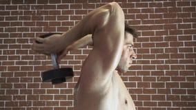Uomo forte che fa esercizio con le teste di legno video d archivio