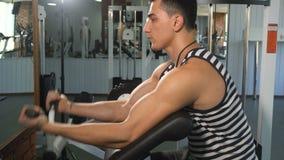 Uomo forte che fa esercizio in macchina del bicipite video d archivio