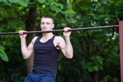 Uomo forte che fa tirata-UPS su una barra all'aperto Fotografie Stock Libere da Diritti