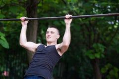 Uomo forte che fa tirata-UPS su una barra all'aperto Fotografia Stock Libera da Diritti