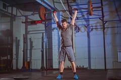 Uomo forte che fa un esercizio con un bilanciere nella palestra su un fondo di un muro di cemento grigio Fotografie Stock Libere da Diritti
