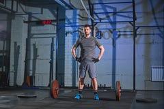 Uomo forte che fa un esercizio con un bilanciere nella palestra su un fondo di un muro di cemento grigio Immagine Stock