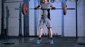 Uomo forte che fa un esercizio con un bilanciere nella palestra su un fondo di un muro di cemento grigio archivi video