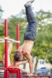 Uomo forte che sta sulle mani su una barra trasversale su un fondo del parco Concetto di allenamento Immagini Stock
