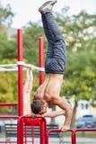 Uomo forte che sta sulle mani su una barra trasversale su un fondo del parco Concetto di allenamento Immagine Stock