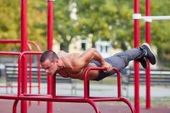 Uomo forte che sta sulle mani su una barra trasversale su un fondo del parco Concetto di allenamento Immagine Stock Libera da Diritti