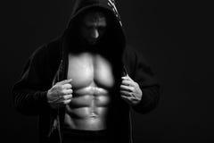 Uomo forte nel cappuccio che mostra il suo stampa su fondo nero Fotografia Stock