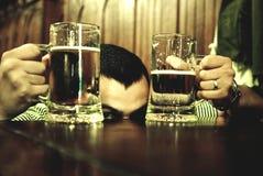 Uomo fra i vetri di birra Fotografia Stock