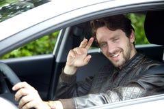 Uomo fresco che conduce automobile che dice ciao che guarda macchina fotografica Immagine Stock