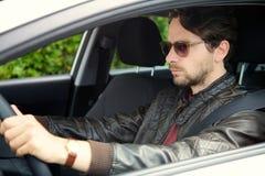 Uomo fresco con i vetri di sole che conducono automobile Immagine Stock Libera da Diritti