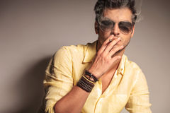 Uomo fresco di modo con gli occhiali da sole che gode della sua sigaretta Fotografie Stock