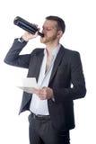 Uomo frustrato che beve e che esamina le fatture Immagine Stock