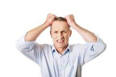 Uomo frustrato che tira i suoi capelli fotografia stock