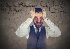 Uomo frustrato di affari contro i grafici marroni della pioggia e del fondo Immagine Stock