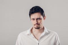 Uomo frustrato ed irritato dei giovani bei in camicia bianca su fondo grigio morbido, luce fotografie stock
