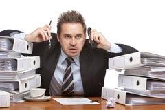 Uomo frustrato sollecitato di affari con i telefoni immagine stock libera da diritti