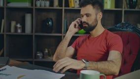 Uomo furioso che parla sul telefono allo scrittorio Uomo arrabbiato di affari che parla sul telefono cellulare stock footage