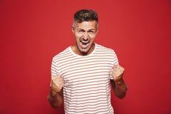 Uomo furioso emozionale in maglietta a strisce che grida e che mostra f immagine stock