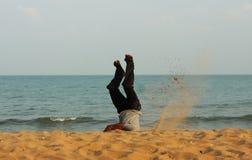 Uomo gambe all'aria sulla spiaggia in India Immagine Stock