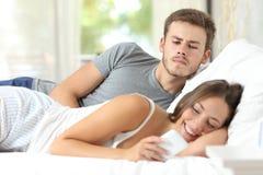 Uomo geloso del gossip che guarda il suo telefono cellulare della moglie Fotografia Stock