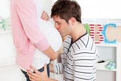 Uomo gentile che bacia la pancia della sua moglie incinta fotografia stock libera da diritti