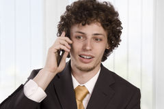 Uomo gesturing felice di affari con il telefono mobile Fotografie Stock Libere da Diritti