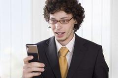 Uomo gesturing felice di affari con il telefono mobile Immagine Stock