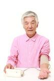 Uomo giapponese senior che controlla la sua pressione sanguigna Fotografie Stock