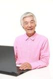 Uomo giapponese senior che per mezzo del computer portatile Fotografie Stock Libere da Diritti