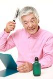 uomo giapponese senior che usando il restauratore di capelli Immagini Stock Libere da Diritti