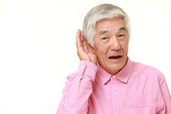Uomo giapponese senior con la mano dietro l'orecchio che ascolta molto attentamente Fotografia Stock Libera da Diritti