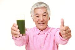 Uomo giapponese senior con succo di verdura verde Fotografia Stock