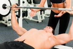 Uomo in ginnastica che si esercita con il barbell Fotografia Stock