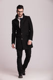 Uomo giovane bello di affari che porta un cappotto nero lungo fotografia stock libera da diritti