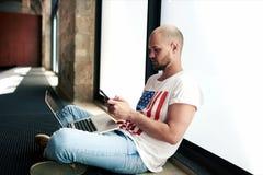 Uomo giovane delle free lance che si collega alla radio tramite taccuino e telefono cellulare Fotografia Stock Libera da Diritti