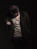 Uomo giovane di modo che controlla il suo cappotto per vedere se c'è il prezzo da pagare Fotografia Stock