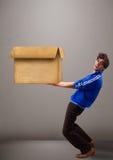 uomo Goog di aspetto che tiene una scatola di cartone marrone vuota Fotografie Stock Libere da Diritti