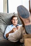 Uomo in grande sedia che manda un sms con il telefono Fotografia Stock