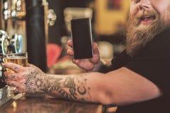Uomo grasso allegro che mostra il suo microtelefono con il sorriso immagini stock libere da diritti