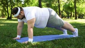 Uomo grasso che fa plancia, preparantesi all'aperto, desiderio di essere esile, forza di volontà di motivazione fotografia stock
