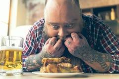 Uomo grasso che fissa alla carne con appetito Fotografie Stock