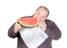 Uomo grasso che rimbocca nell'anguria Fotografie Stock Libere da Diritti