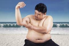 Uomo grasso che tiene il suo bicipite floscio fotografia stock libera da diritti