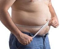 Uomo grasso che tiene un nastro di misura Fotografia Stock