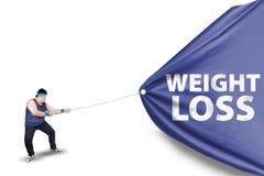 Uomo grasso che tira un'insegna 2 di perdita di peso Fotografie Stock