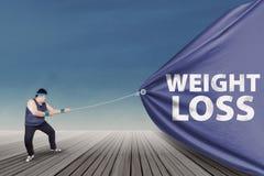 Uomo grasso che tira un'insegna 1 di perdita di peso Fotografia Stock Libera da Diritti